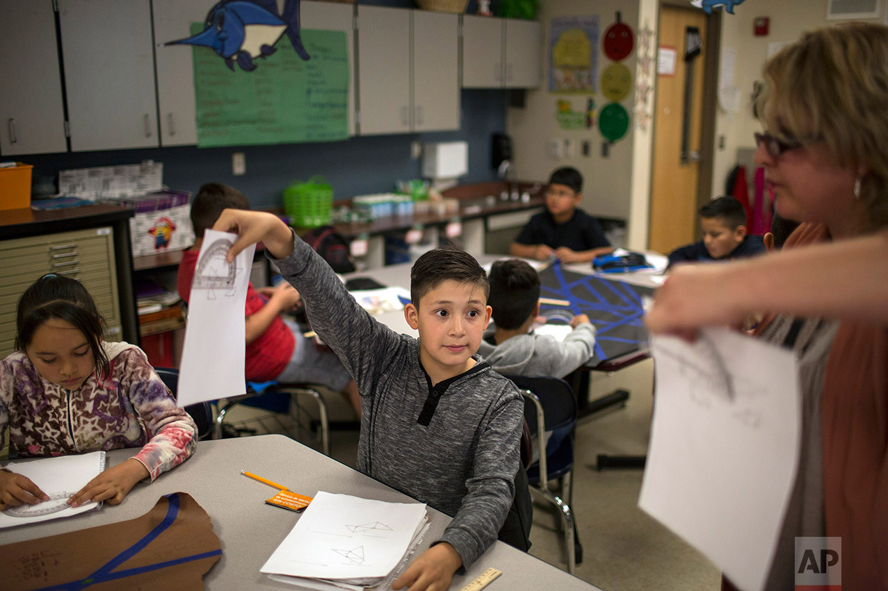 A fifth grade student shows his geometry work to a teacher at Columbus Elementary School, in Columbus, New Mexico, Friday, March 31, 2017. (AP Photo/Rodrigo Abd)