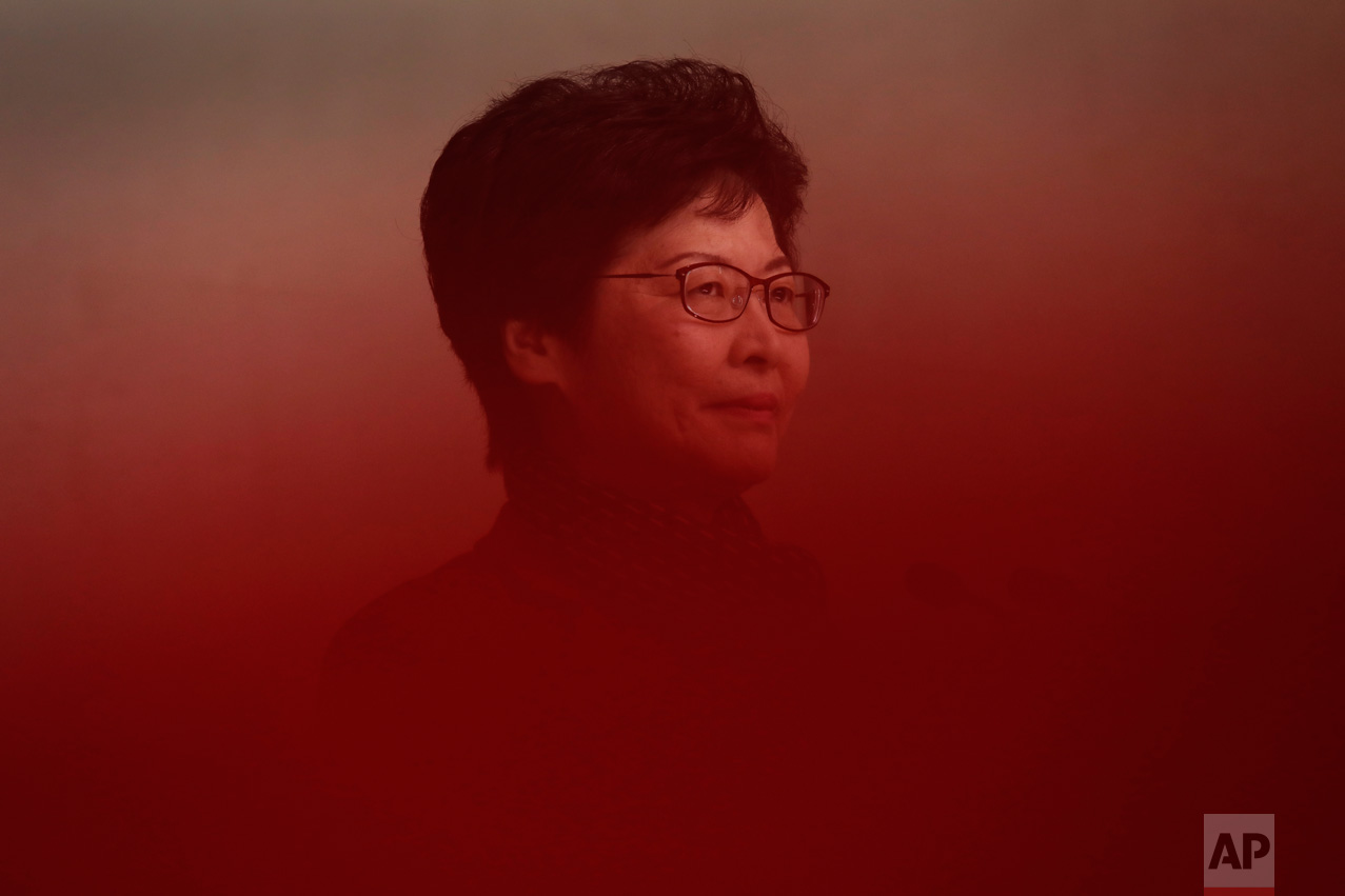 Hong Kong's chief executive elect Carrie Lam stands behind a red ribbon before making a statement after meeting with current chief executive Leung Chun-ying at government headquarters in Hong Kong, Monday, March 27, 2017. The candidate favored by China's Communist leadership was chosen as Hong Kong's new leader a day earlier, in the first such vote since huge pro-democracy protests erupted over the semiautonomous Chinese city's election system in 2014. (AP Photo/Vincent Yu)