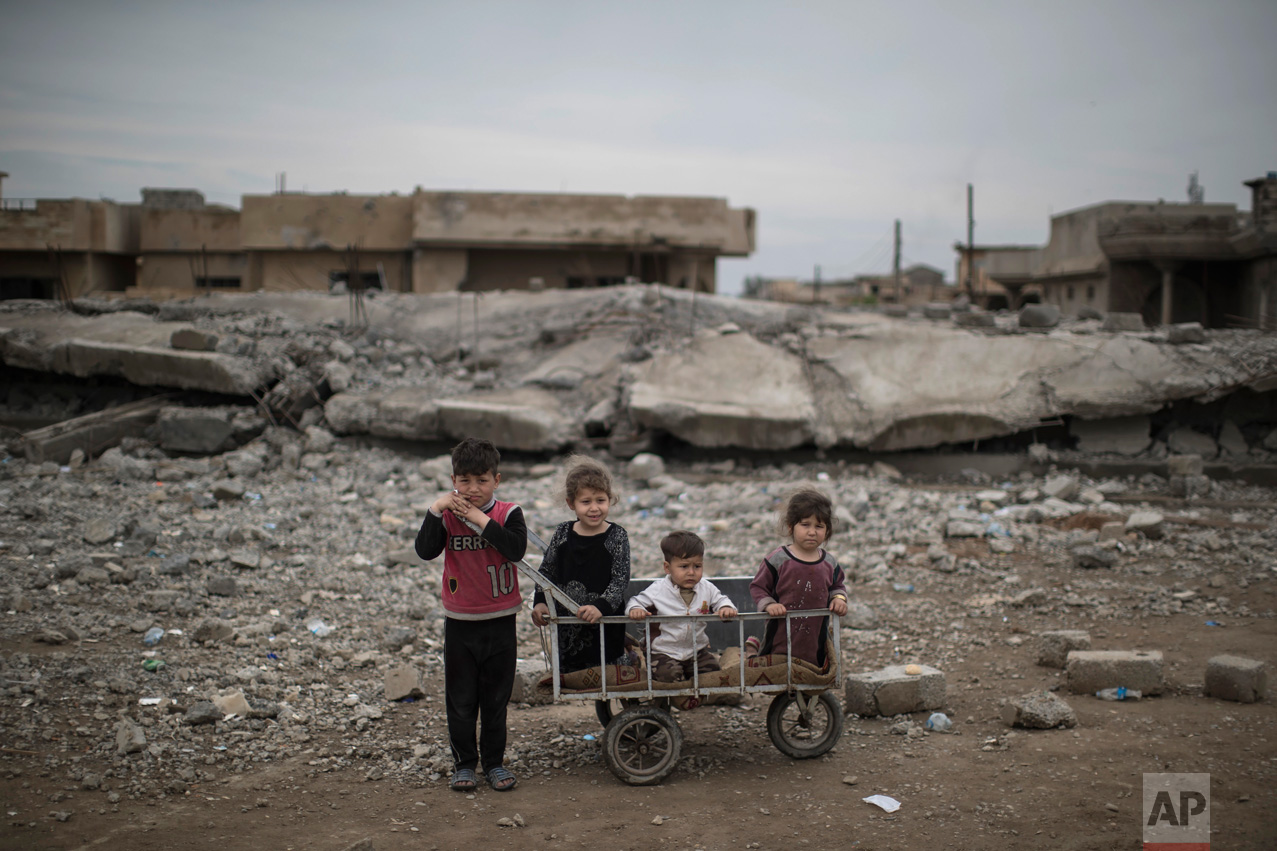 Children wait as their mother collects food being distributed in a neighborhood recently retaken by Iraqi security forces from Islamic State militants on the western side of in Mosul, Iraq, Friday, March 31, 2017. (AP Photo/Felipe Dana)