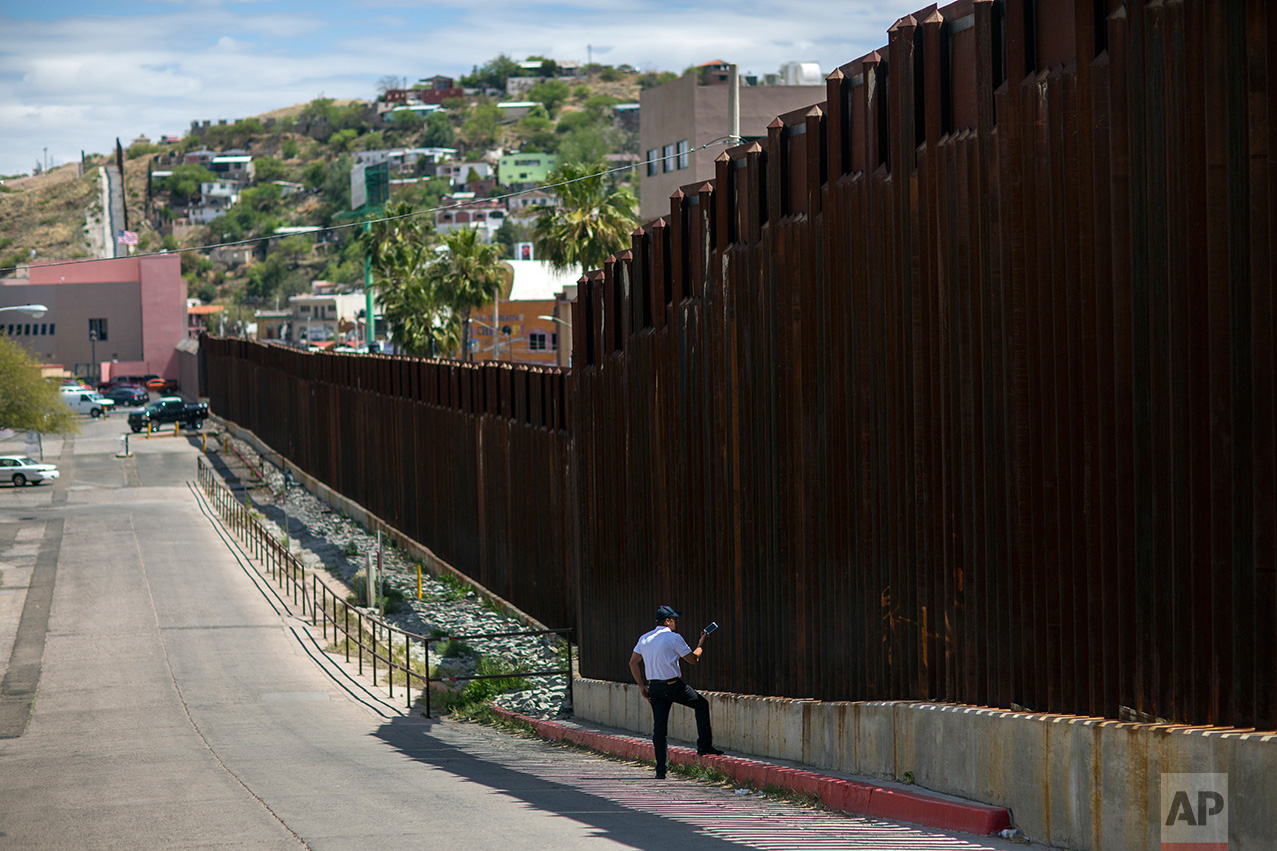 A man in Nogales, Arizona, talks to his daughter and her mother who are standing on the other side of the border fence in Nogales, Mexico, Saturday, April 1, 2017. (AP Photo/Rodrigo Abd)