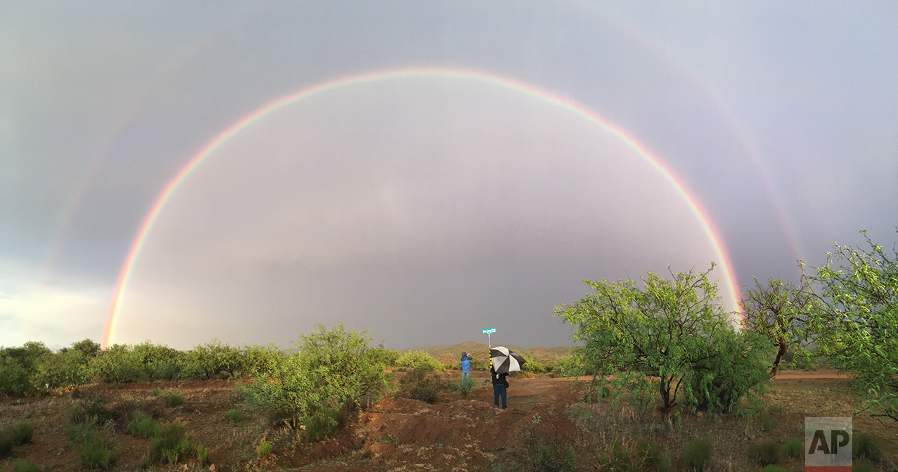 Video journalist Brian Skoloff, left, and AP photographer Rodrigo Abd see a double rainbow on the outskirts of Sasabe, in the Mexican state of Sonora, near the border with Arizona, April 1, 2017. (AP Photo/Christopher Sherman)