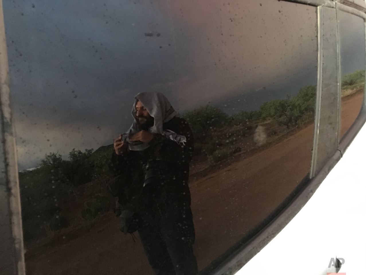 AP photographer Rodrigo Abd is reflected in a car window as he cleans his lens before seeing a double rainbow on the outskirts of Sasabe, in the Mexican state of Sonora, near the border with Arizona, April 1, 2017. (AP Photo/Christopher Sherman)