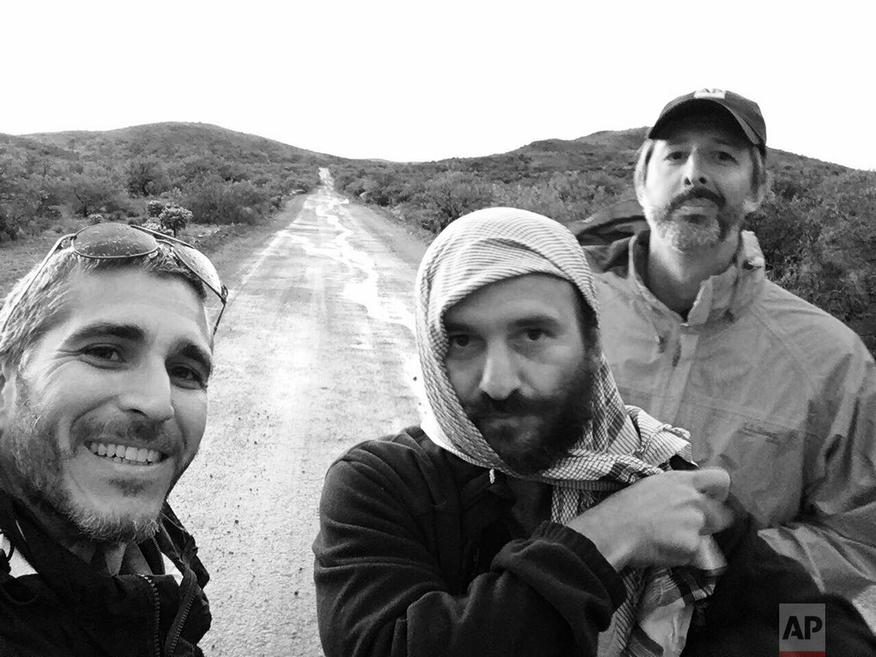 AP video journalist Brian Skoloff, from left, AP photographer Rodrigo Abd and AP correspondent Christopher Sherman, pose fro a group photo on the outskirts of Sasabe, in the Mexican state of Sonora, near the border with Arizona, April 1, 2017. (AP Photo/Brian Skoloff)