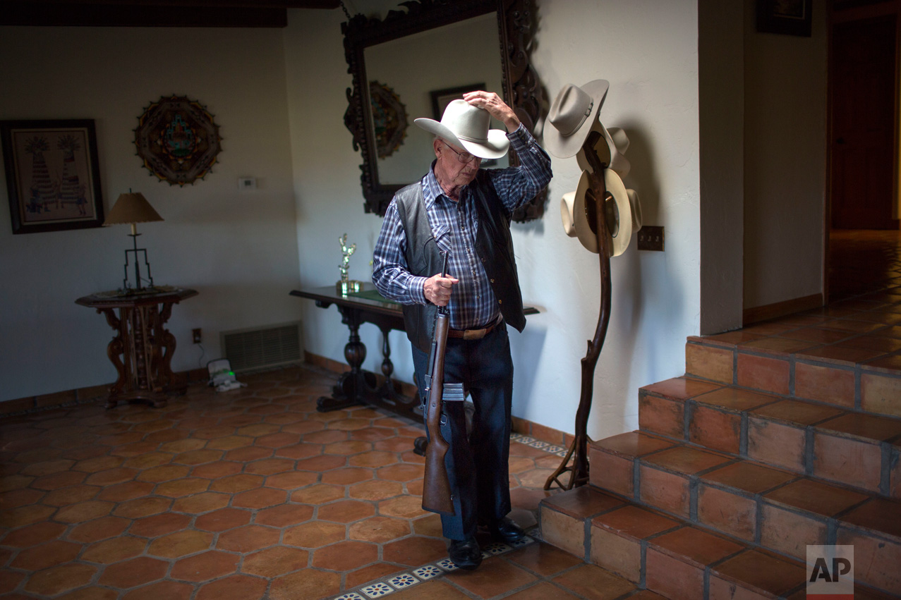 Rancher Jim Chilton puts on his hat before heading out to survey his 50,000-acre ranch in Arivaca, about 80 miles southwest of Tucson, Ariz., Sunday, April 2, 2017. (AP Photo/Rodrigo Abd)