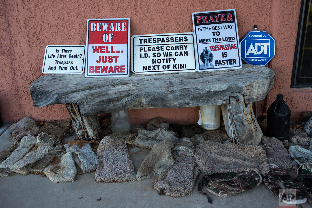 """Signs warning trespassers line a wooden bench surrounded by makeshift slip-ons known as """"carpet shoes"""" on the porch of rancher Jim Chilton, in Arivaca, Ariz., Sunday, April 2, 2017. Chilton, who finds the slip-ons abandoned on his property, says they are worn by people illegally crossing the border as a way to keep authorities from finding their tracks. (AP Photo/Rodrigo Abd)"""