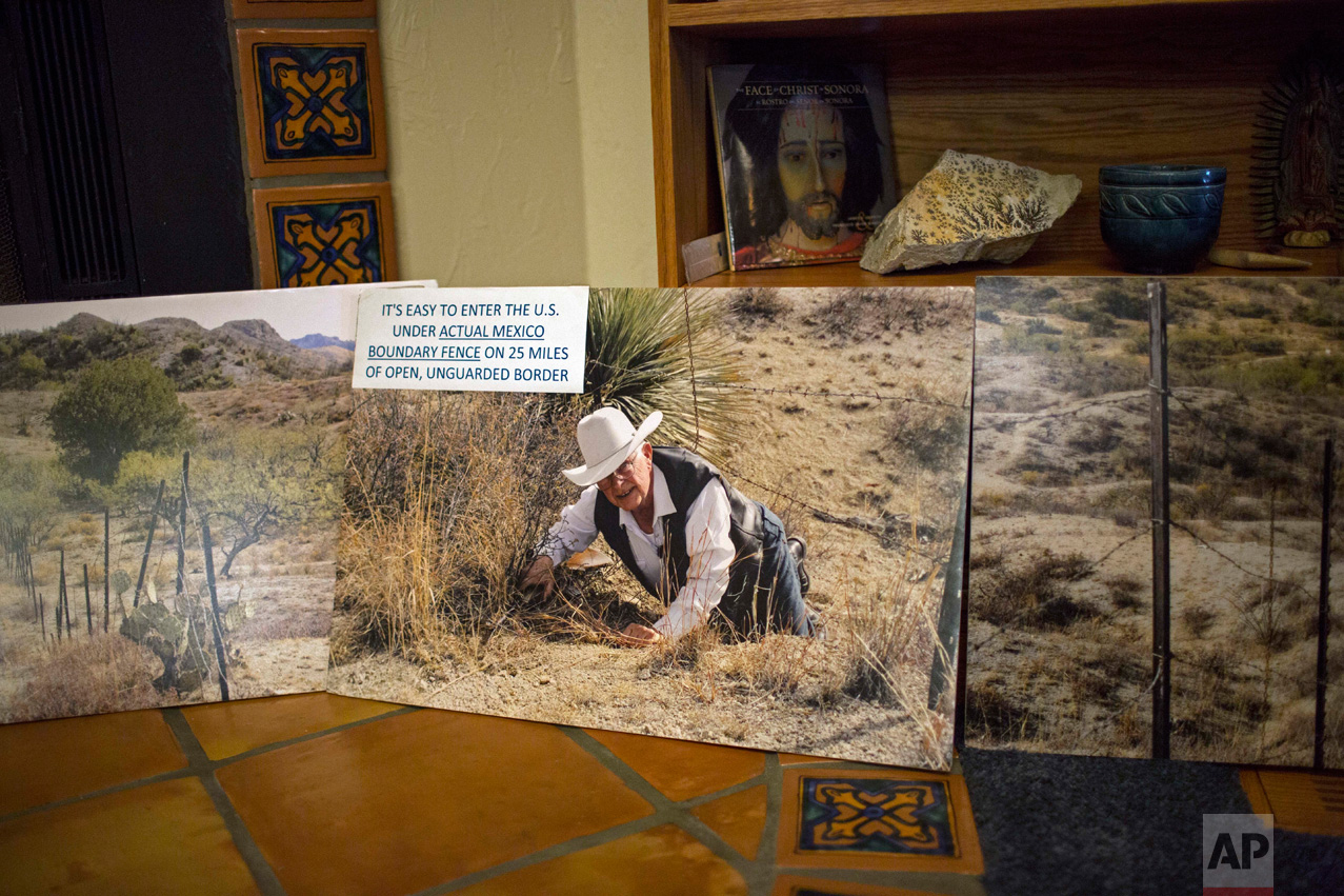 A photo of rancher Jim Chilton showing how easy it is to climb under the existing barbed wire fence on his ranch along the US-Mexico border, is displayed in his home in Arivaca, Ariz., Sunday, April 2, 2017. (AP Photo/Rodrigo Abd)