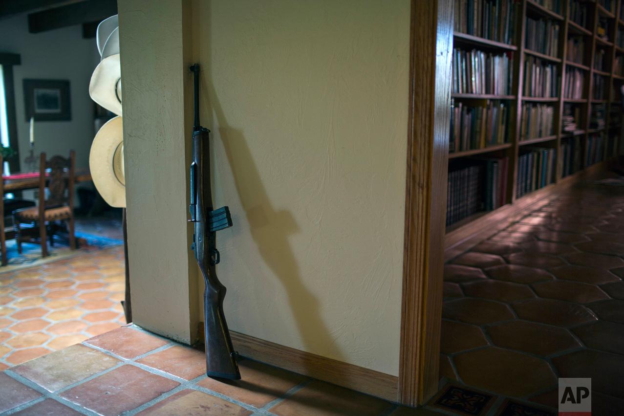 Rancher Jim Chilton's rifle is propped against a wall inside his ranch in Arivaca, Ariz., Sunday, April 2, 2017. (AP Photo/Rodrigo Abd)