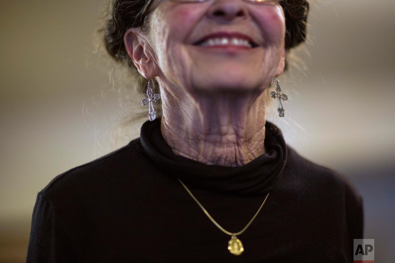 Sue Chilton, the wife of rancher Jim Chilton, dons silver crucifix earrings, as she smiles in their 50,000 acre ranch in Arivaca, Ariz., Sunday, April 2, 2017. (AP Photo/Rodrigo Abd)
