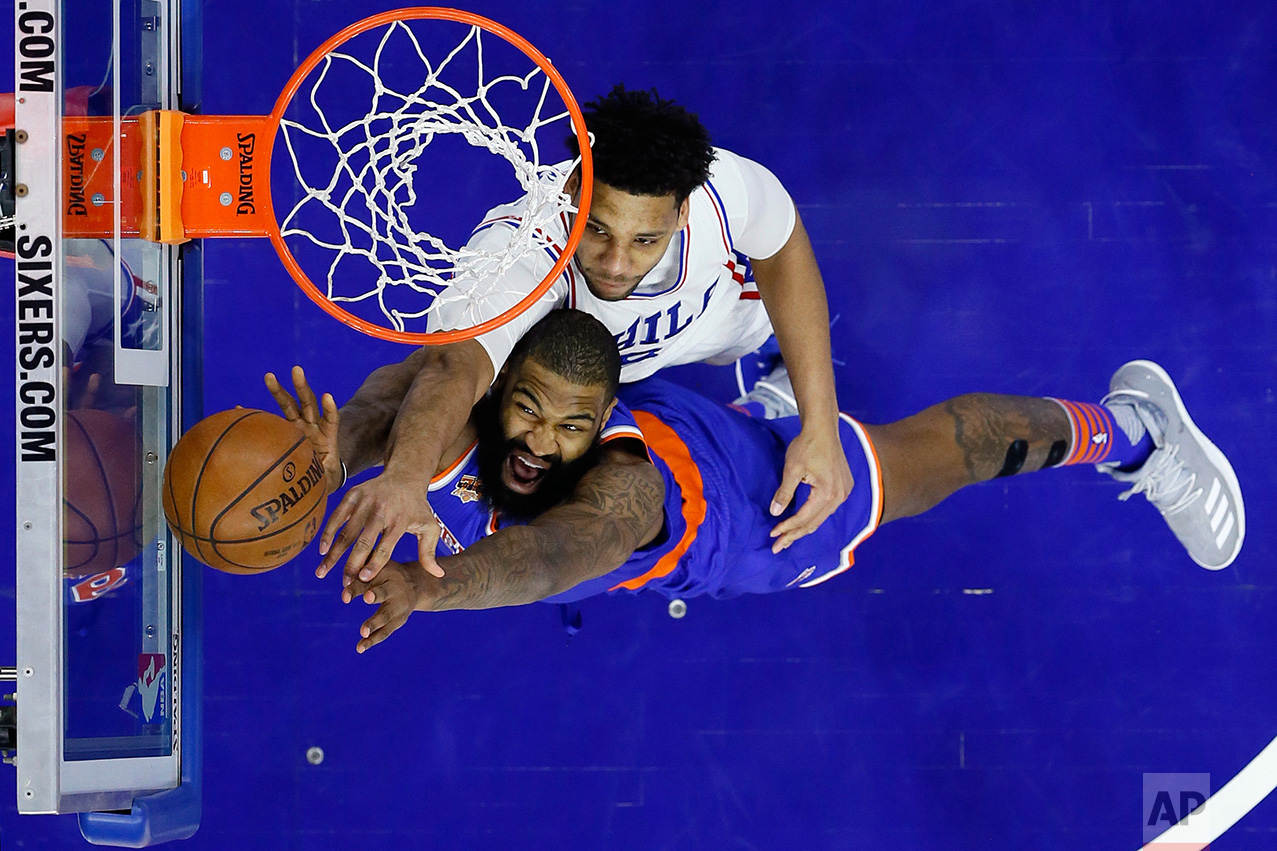 Philadelphia 76ers' Jahlil Okafor, top, and New York Knicks' Kyle O'Quinn leap for a rebound during the second half of an NBA basketball game, Friday, March 3, 2017, in Philadelphia. (AP Photo/Matt Slocum)