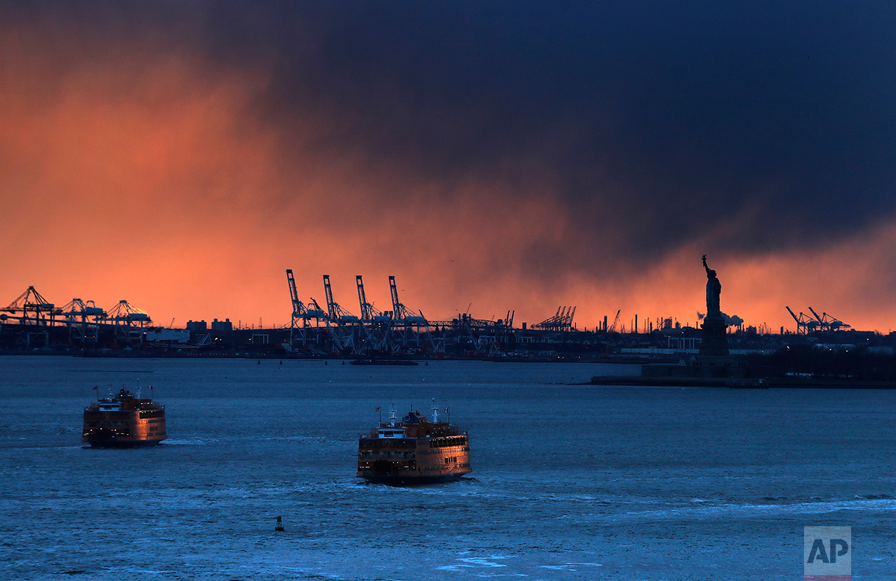 Two Staten Island Ferry boats catch the last rays of the setting sun while crossing paths as one departs from and the other arrives at the lower Manhattan terminal, Friday, March 3, 2017, in New York. (AP Photo/Julie Jacobson)