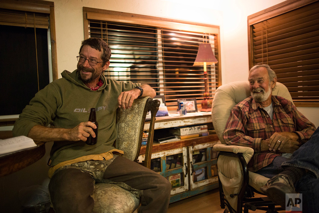 Mark Hainds of Andalusia, Alabama, left, enjoys a beer at the end of a day's walk in the home of archeologist Rick Martynec in Why, Arizona, Monday, April 3, 2017. (AP Photo/Rodrigo Abd)