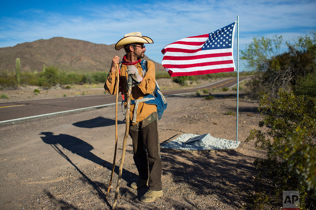 Mark Hainds of Andalusia, Alabama, stands next to a road memorial for a Border Patrol agent killed in a car accident, near Why, Ariz., Monday, April 3, 2017. Hainds is attempting to walk the length of the U.S.-Mexico border. (AP Photo/Rodrigo Abd)