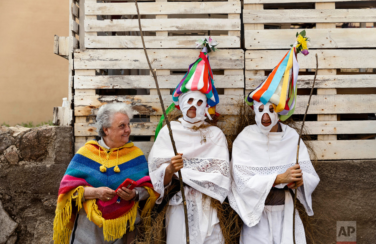 In this April 1, 2017 picture, a woman speaks with a couple of youngsters dressed as 'Zarramaches' a character from the traditional carnival of Casavieja, during a gathering of different villages' carnival masks and characters, in Casavieja, Spain, Monday, April 3, 2017. These festivals, held across central and northwestern Spain, most often coincide with festivities celebrating the advent of spring, mixing Carnival and bizarre pagan-like rituals with mock battles between good and evil.(AP Photo/Daniel Ochoa de Olza)