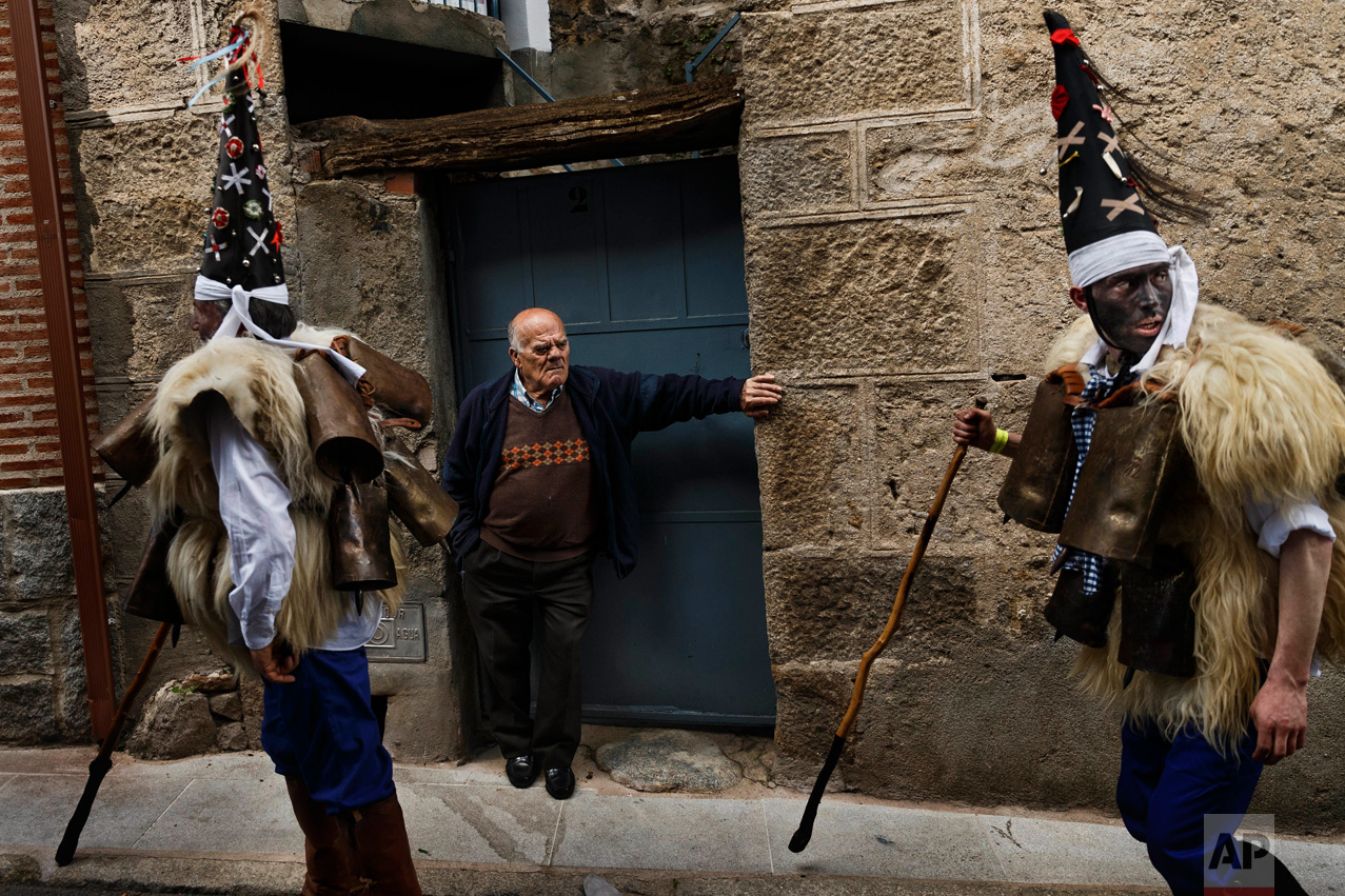 In this April 1, 2017 picture, a man looks as 'Zarramacos' dong their cowbells in a representation of the traditional carnival of La Vijanera de Silio during a gathering of different villages' carnival masks and characters, in Casavieja, Spain, Monday, April 3, 2017. (AP Photo/Daniel Ochoa de Olza)