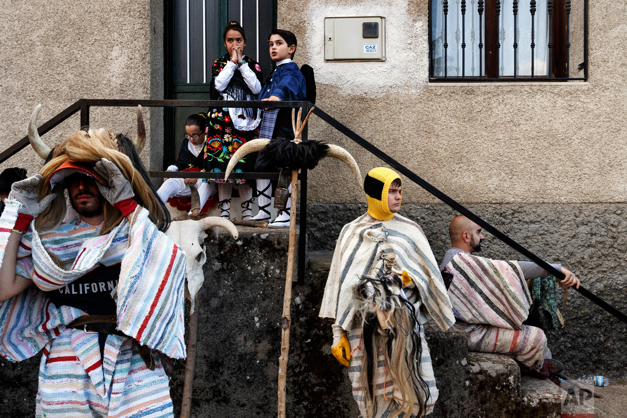 In this April 1, 2017 picture revelers from Navalosa village wearing the traditional 'Cucurrumacho' mask and outfit rest after a parade during a gathering of different villages' carnival masks and characters in the small village of Casavieja, Spain, Monday, April 3, 2017. (AP Photo/Daniel Ochoa de Olza)