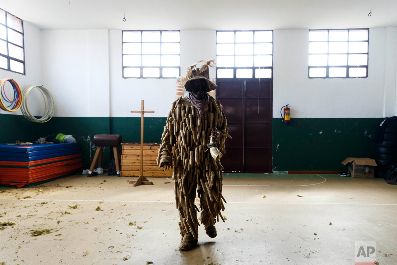 In this April 1, 2017 picture, a man dressed as a 'Trapajon' and representing a natural entity walks in the village's gym used as a changing room after a traditional Spanish mask gathering in the small village of Casavieja, Spain, Monday, April 3, 2017. (AP Photo/Daniel Ochoa de Olza)