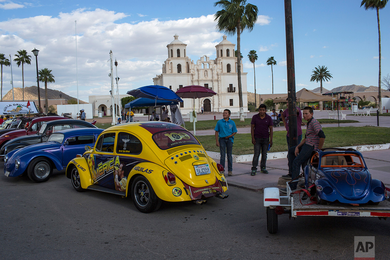 People gather for a car show featuring Volkswagen Beetles, known as 'bochos' by locals, in Caborca, in the Mexican state of Sonora, Saturday, April 1, 2017. Caborca lies in traditional tribal lands of the Tohono O'odham indigenous people, a region that straddles the U.S.-Mexico border in the states of Arizona and Sonora.(AP Photo/Rodrigo Abd)