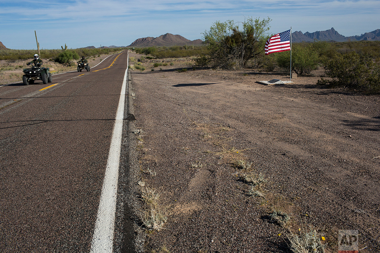 Border Patrol agents on patrol ride past a road memorial dedicated to a fellow agent killed in a car accident near Why, Ariz., Monday, April 3, 2017.  (AP Photo/Rodrigo Abd)