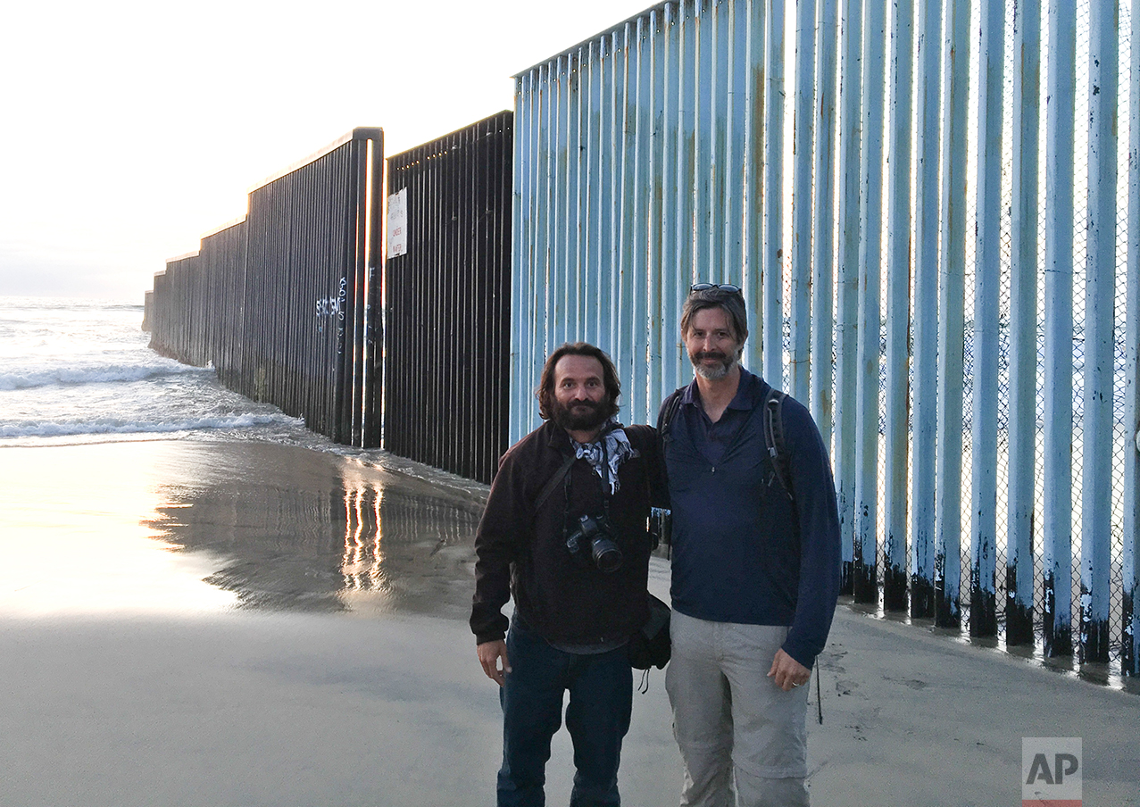 In this Tuesday, April 4, 2017 photo, Associated Press photographer Rodrigo Abd and correspondent Christopher Sherman, pose for a photo at the end of their 3,000 mile journey, backdropped by the US-Mexico border fence that separates Tijuana, Mexico, from San Diego, Calif. (AP Photo)