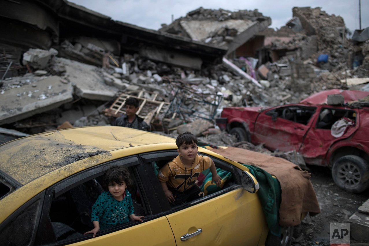 Children play inside a damaged car, amid heavy destruction in a neighborhood recently retaken by Iraqi security forces from Islamic State militants on the western side of Mosul, Iraq, Saturday, April 1, 2017. (AP Photo/Felipe Dana)
