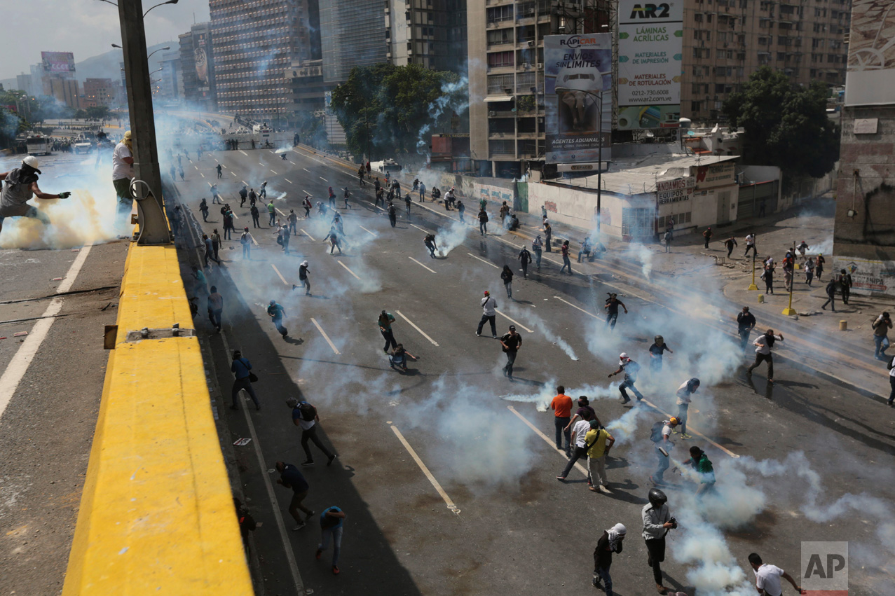 Demonstrators throw back tear gas canisters shot by riot police during a protest in Caracas, Venezuela, Thursday, April 6, 2017. The country has seen near-daily protests since the Supreme Court issued a ruling nullifying congress a week earlier. The court pulled that decision back after it came under heavy criticism, but opposition leaders said the attempt to invalidate a branch of power revealed the administration's true dictatorial nature. (AP Photo/Fernando Llano)