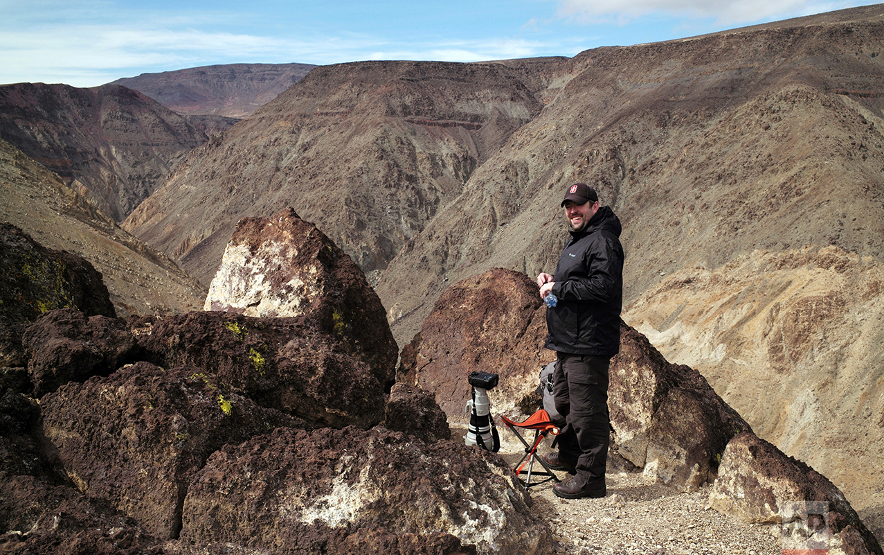 In this photo taken Feb. 28, 2017, photographer Jason O. Watson waits on a cliff overlooking the nicknamed Star Wars Canyon in Death Valley National Park, Calif. Military jets roaring over national parks have long drawn complaints from hikers and campers. (AP Photo/Ben Margot)
