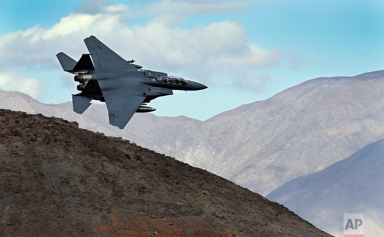 In this Feb. 27, 2017, photo an F-15E Strike Eagle from Seymour Johnson AFB in North Carolina flies out of the nicknamed Star Wars Canyon turning toward the Panamint range over Death Valley National Park, Calif. (AP Photo/Ben Margot)