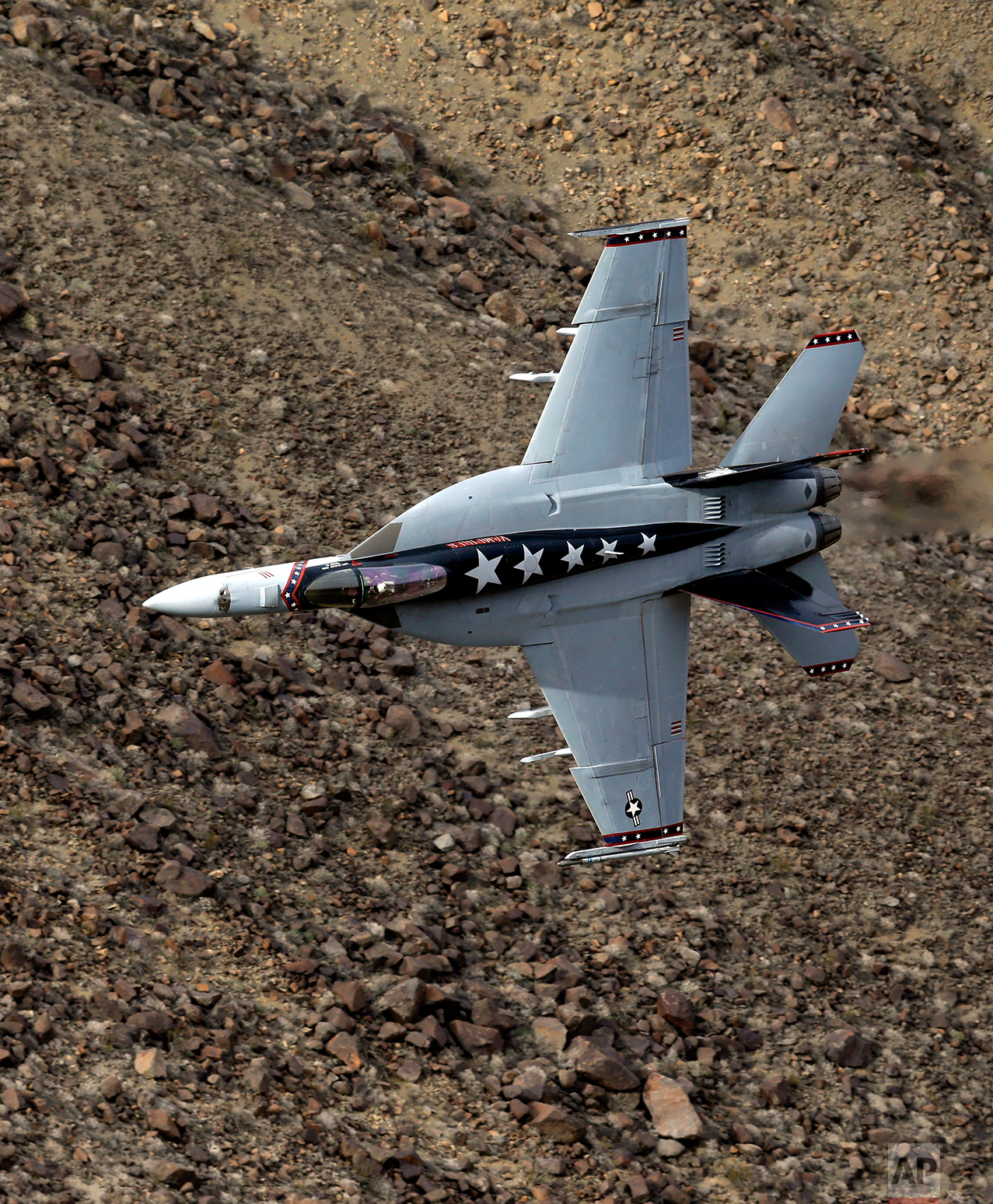 """In this Feb. 27, 2017, photo, Lt. Cmdr. Ian """"Elf"""" Kibler of the VX-9 Vampire squadron from Naval Air Weapons Station, China Lake, banks his F/A-18E Super Hornet through the nicknamed Star Wars Canyon in Death Valley National Park, Calif. (AP Photo/Ben Margot)"""