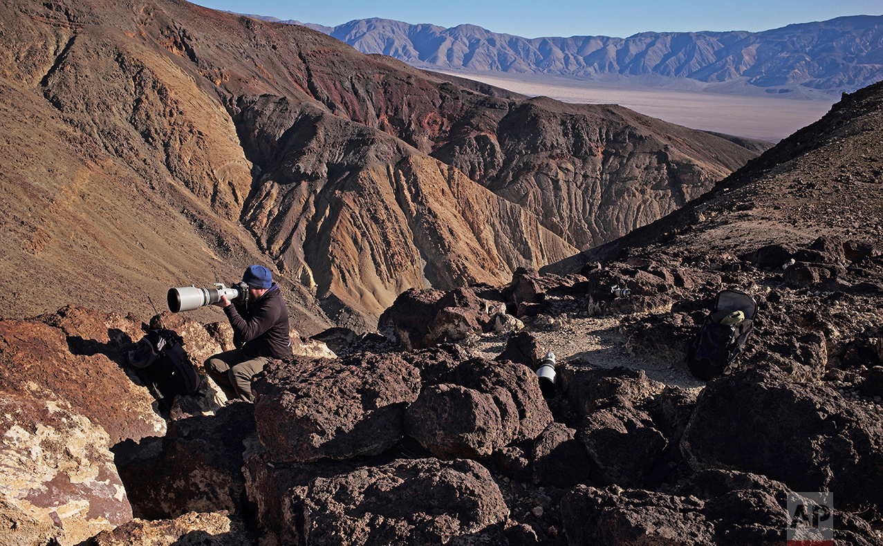 In this Feb. 28, 2017, photo, Jason O. Watson looks through a telephoto lens on a cliff overlooking the nicknamed Star Wars Canyon in Death Valley National Park, Calif. (AP Photo/Ben Margot)