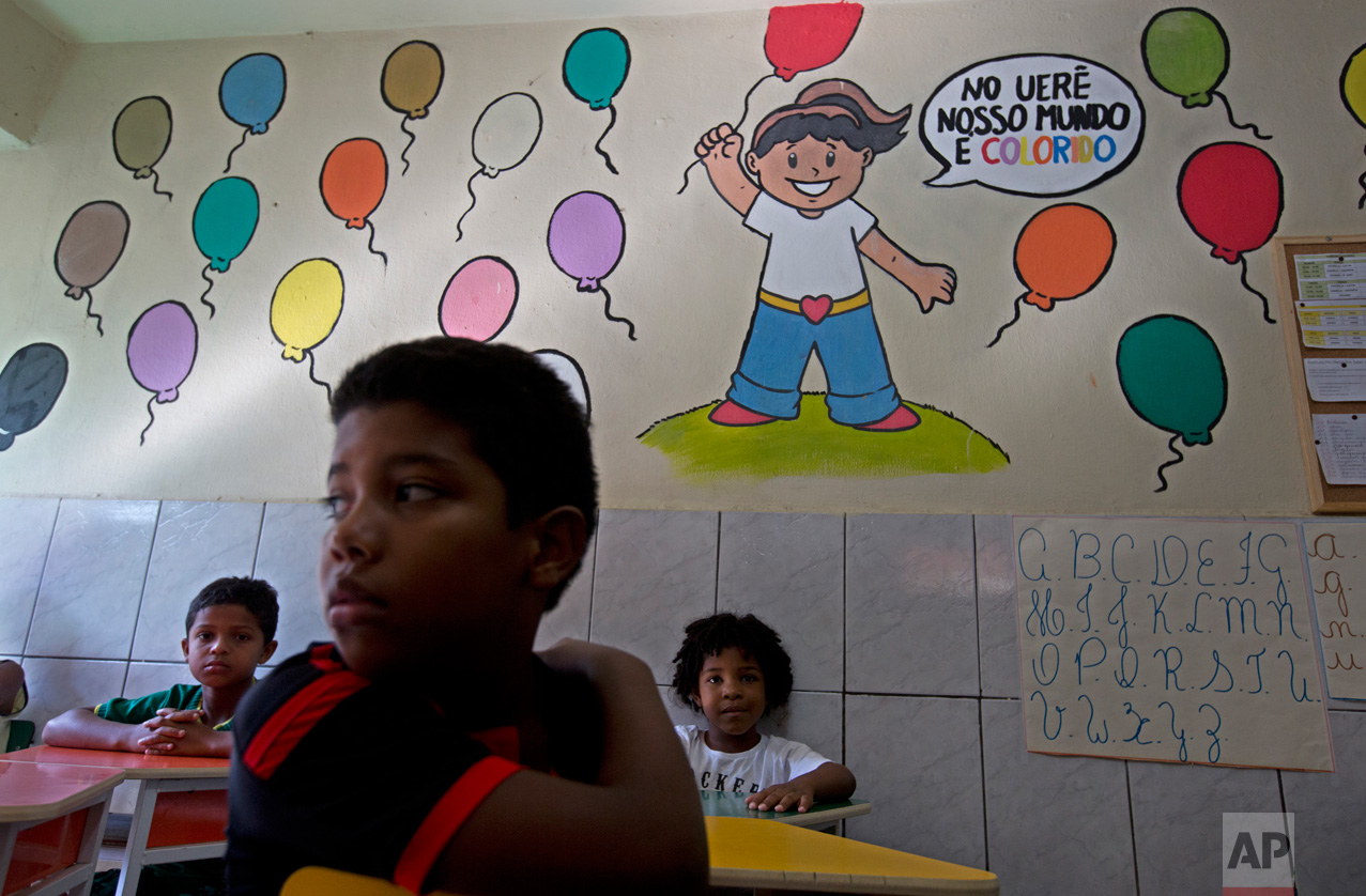In this April 5, 2017 photo, students sit in their classroom at the Uere special needs school in the Mare slum in Rio de Janeiro, Brazil. At least 10 times in the last two months, crackling gunfire just outside Uere has sent students and teachers diving to the floor, as heavily armed gangsters warred among themselves and sometimes with police. (AP Photo/Silvia Izquierdo)