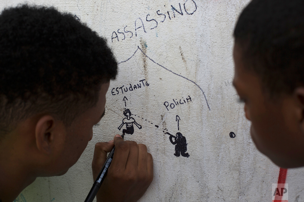 In this March 31, 2017 photo, a boy makes a drawing depicting a police officer shooting at a student on the wall of the school where 13-year-old girl Maria Eduarda Conceicao was killed by a stray bullet during a shootout between police and alleged drug traffickers, in Rio de Janeiro, Brazil. Large bullet holes can still be seen on the school's outer wall and front gate, a grim reminder for students, teachers and parents walking in every day. (AP Photo/Leo Correa)