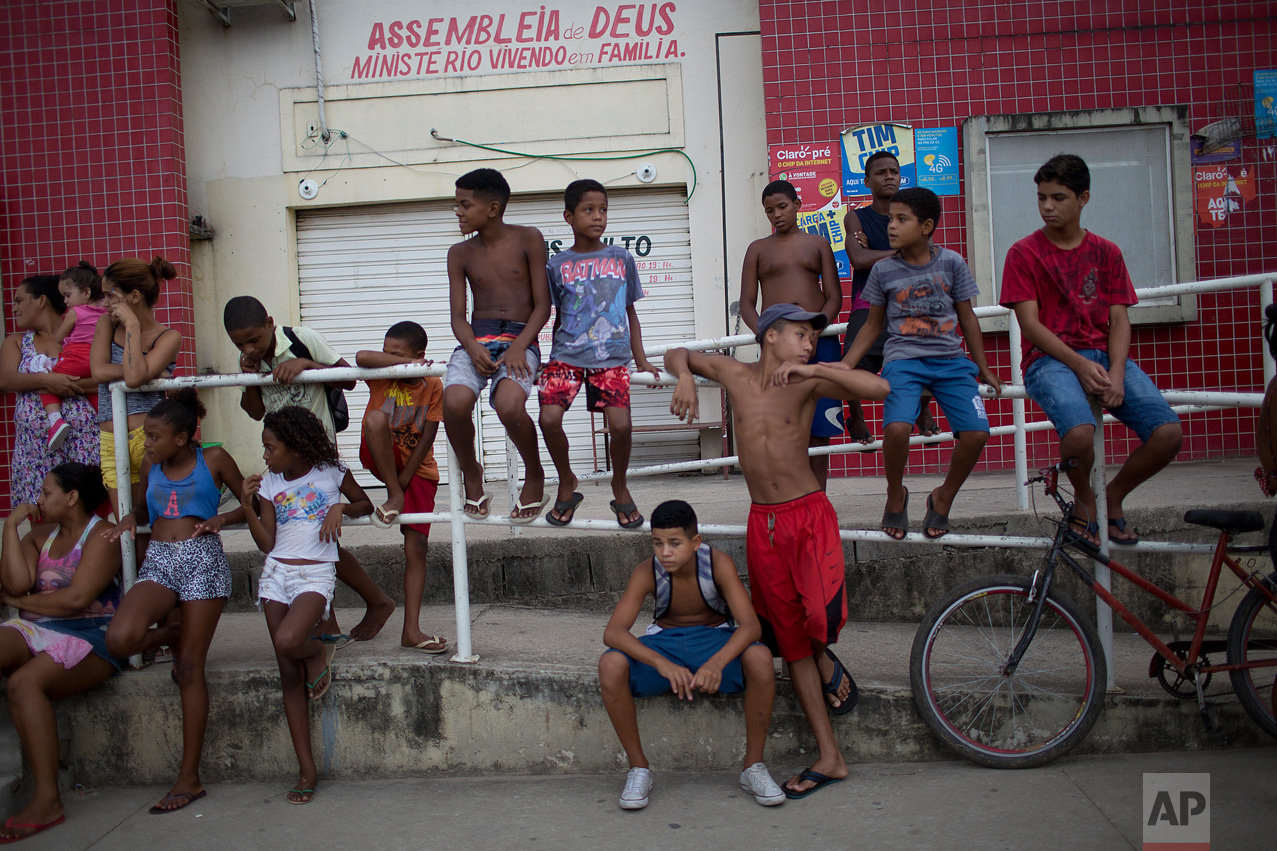 In this April 12, 2017 photo, children hang out near the school where a 13-year-old student was shot and killed during a shootout between police and alleged drug traffickers in Acari, Rio de Janeiro, Brazil. In Rio's violent slums, schools are increasingly caught in the crossfire as gangs and police shoot it out. (AP Photo/Silvia Izquierdo)