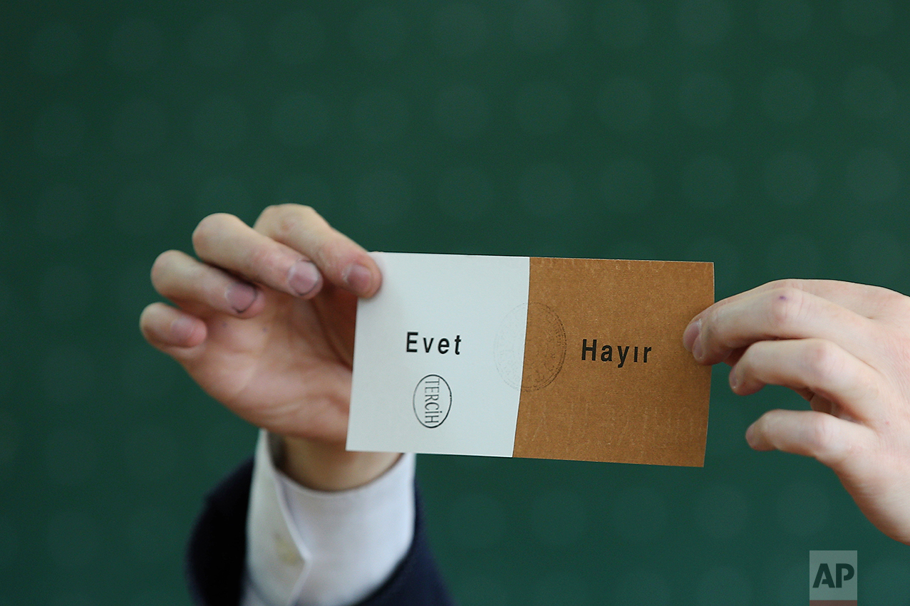 """A member of an electoral committee holds a ballot stamped in favor of """"Yes"""" inside a polling station in Istanbul, on Sunday, April 16, 2017. (AP Photo/Emrah Gurel)"""