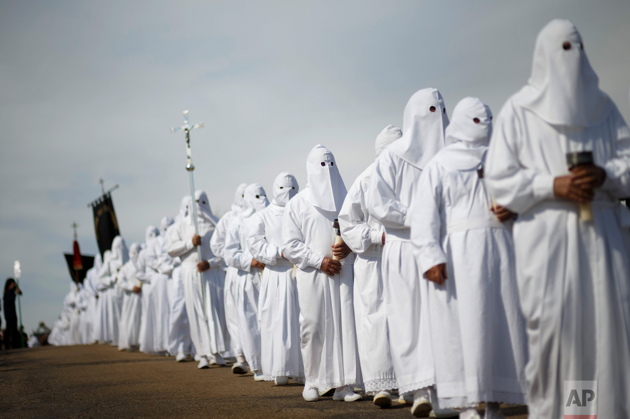 In this Friday, April 14, 2017 photo, penitents from the 'El Santo Entierro' brotherhood take part in a procession in the small village of Bercianos de Aliste, northwestern Spain. For days leading up to Easter Sunday each year, hundreds of colorful processions featuring penitents and magnificently decorated religious floats parade through villages and cities across the country, celebrating the Passion of Christ from the crucifixion to resurrection, celebrations which have become a major tourist attraction and televised nationwide. (AP Photo/Daniel Ochoa de Olza)