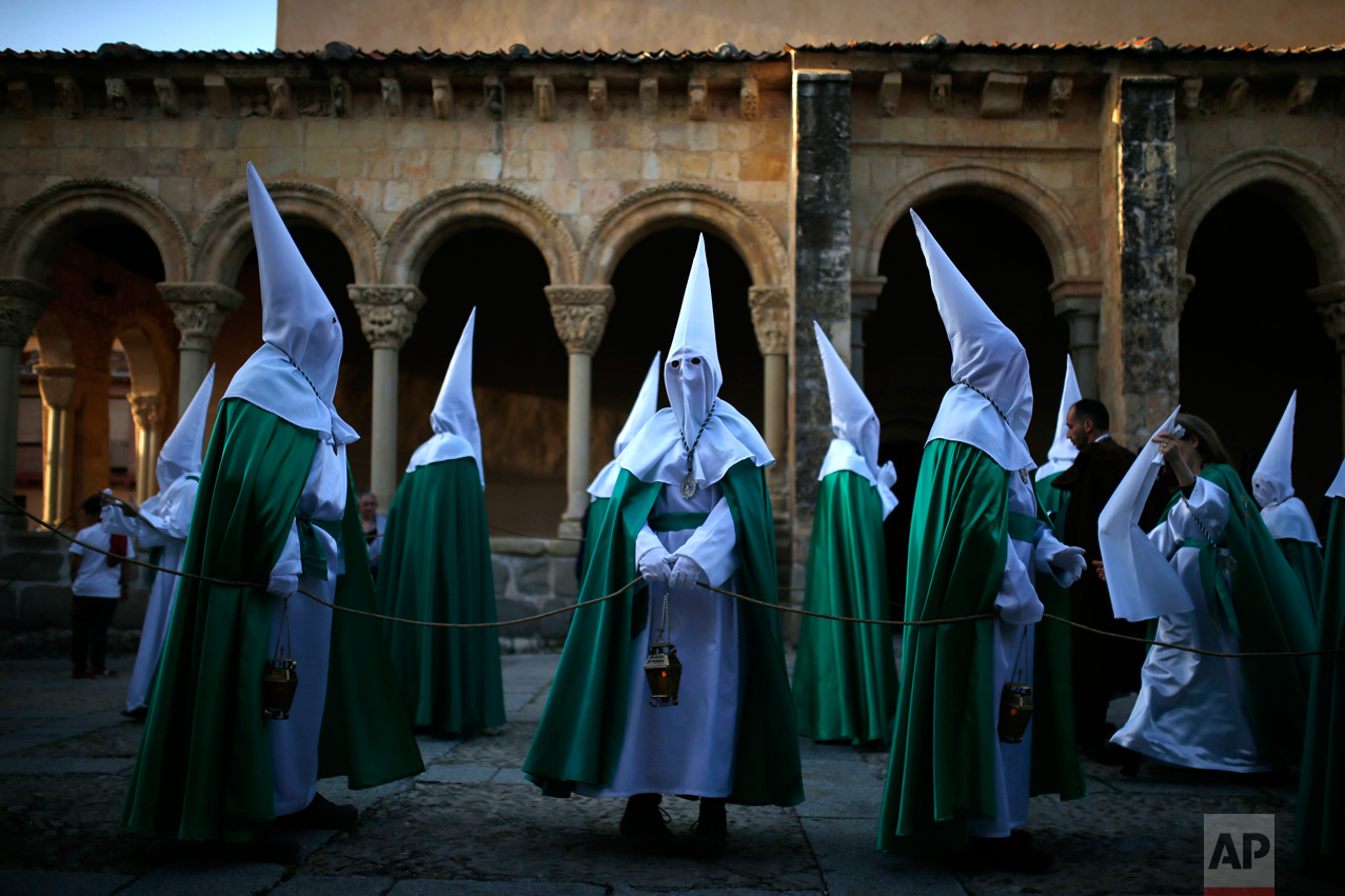 "In this Thursday, April 13, 2017 photo, hooded penitents from ""La Oracion en el Huerto"" brotherhood stand by the San Lorenzo church before taking part in a traditional annual Holy Week procession in Segovia, Spain. (AP Photo/Francisco Seco)"