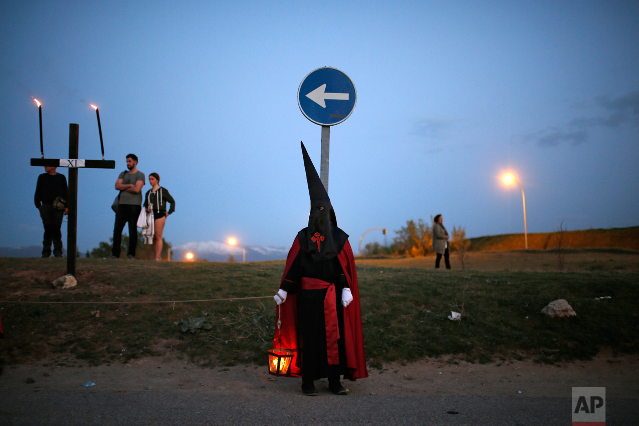 "In this Thursday, April 13, 2017 photo, a hooded penitent from ""Jesus con la Cruz a Cuestas"" brotherhood holds a lantern with a candle as taking part in a traditional annual Holy Week procession in Segovia, Spain. (AP Photo/Francisco Seco)"