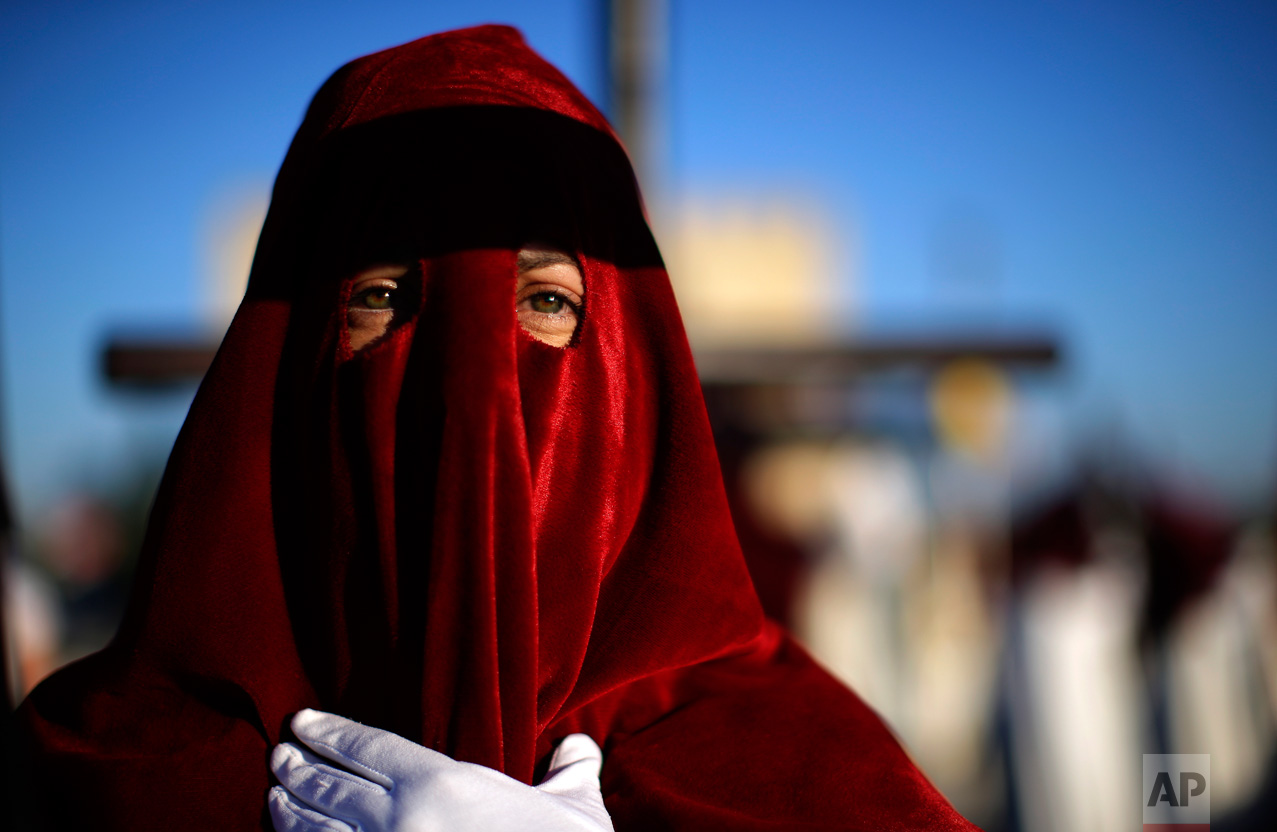 "In this Monday, April 10, 2017 photo, a hooded penitent from ""Vera Cruz"" brotherhood takes part during a Holy Week procession in Cordoba, Spain. (AP Photo/Manu Fernandez)"
