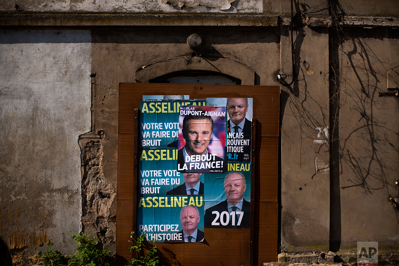 In this Tuesday April 4, 2017 photo, a poster showing a portrait of an independent candidate for the 2017 French Presidential election Nicolas Dupont Aignan is pasted next to others showing François Asselineau, candidate of the UPR party (Union populaire républicaine ie Popular Republican Union) on a wall of a former factory on the outskirts of Hayange. In eastern France's industrial rustbelt, workers are massing behind the virulently nationalistic politics of populist Marine Le Pen. A large chunk of them will come from once left-leaning industrial towns like Hayange, scarred by the closure of its blast furnaces. (AP Photo/Emilio Morenatti)