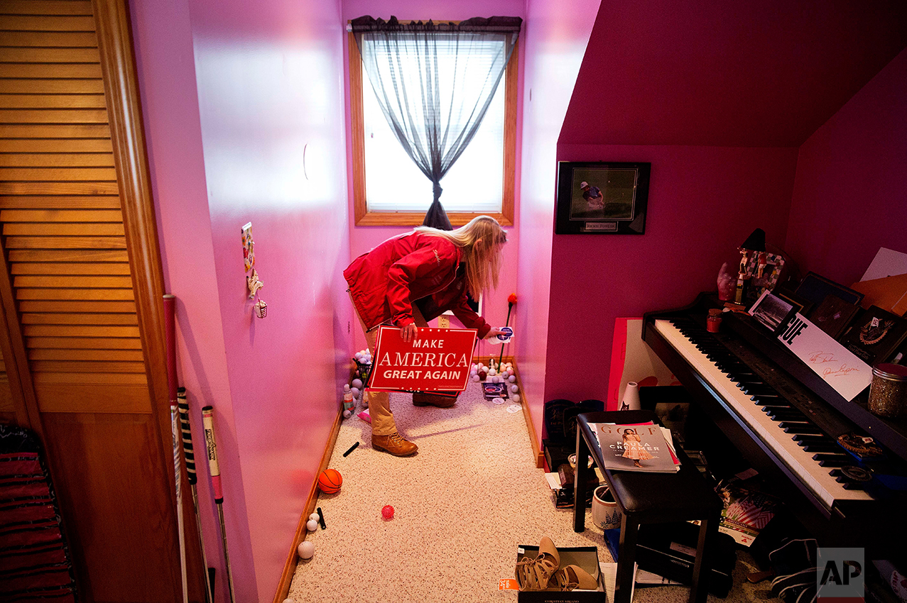 """Trump supporter Stephanie Rodrigue, 17, picks up one of the campaign signs she's collected in her room in Lewiston, Maine, Thursday, March 16, 2017. Although too young to vote, Rodrigue supported Trump, so much she bellowed his name at pep rallies, affixed a campaign sticker to her laptop and came to be called by her classmates """"the mini-Trump."""" (AP Photo/David Goldman)"""