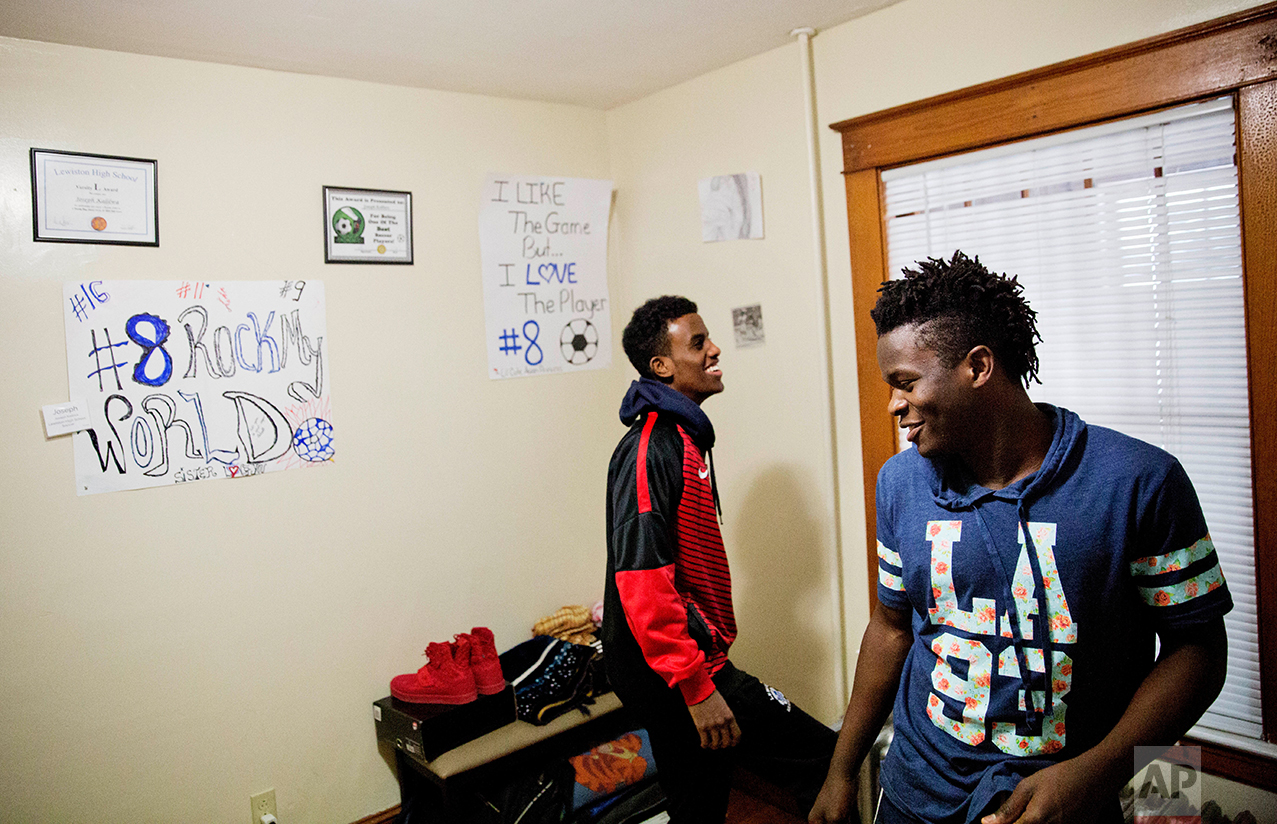 """Lewiston high school seniors and co-captains of the soccer team, Joseph Kalilwa, 18, right, and Abdiaziz Shaleh, 19, play in Kaliwa's room at his home in Lewiston, Maine, Tuesday, March 14, 2017. """"I mean that kind of bothers me sometimes like when people you go everywhere they just see you as a refugee,"""" said Kalilwa who was born in the Democratic Republic of Congo and is now an American citizen. """"I'm like oh well, yeah, I am a refugee but then at the same time I see myself as an American."""" (AP Photo/David Goldman)"""