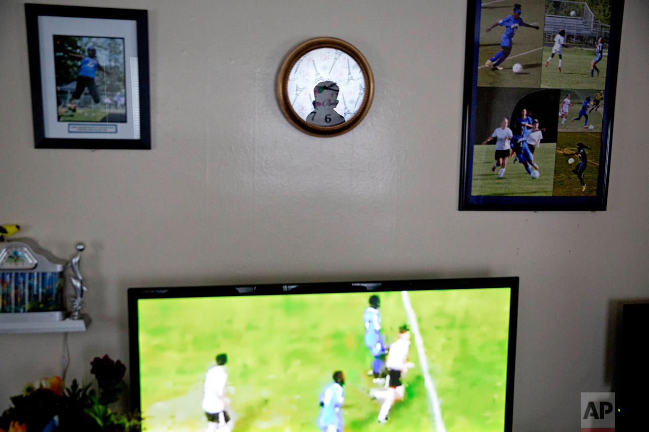 """Abdiaziz Shaleh, 19, a Lewiston high school senior and co-captain of the soccer team is reflected in a clock while watching soccer highlight on television at a friend's house in Lewiston, Maine, Tuesday, March 14, 2017. Shaleh, whose family is from Somalia, waited with them for several years in a refugee camp in Kenya before coming to the United States and eventually settling in Lewiston. Shaleh said President Trump's election has created fear in the refugee community, including among the many students who come from immigrant families. Shaleh also worries about the many refugees who are suffering in Somalia and other parts of Africa, where famine remains a huge issue. """"We got that chance (to come to America),"""" he said. """"I just wanted them to have the same chance."""" (AP Photo/David Goldman)"""