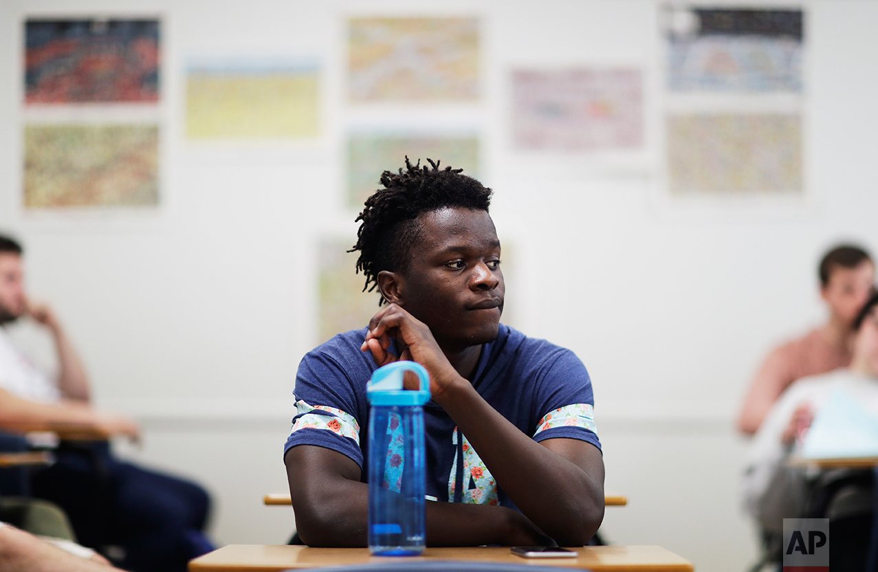 """Lewiston high school senior and co-captain of the soccer team, Joseph Kalilwa, 18, sits in an American government class at Lewiston High School in Lewiston, Maine, Wednesday, March 15, 2017. """"I mean that kind of bothers me sometimes like when people you go everywhere they just see you as a refugee,"""" said Kalilwa of the Democratic Republic of Congo and now an American citizen. """"I'm like oh well yeah I am a refugee but then at the same time I see myself as an American."""" (AP Photo/David Goldman)"""