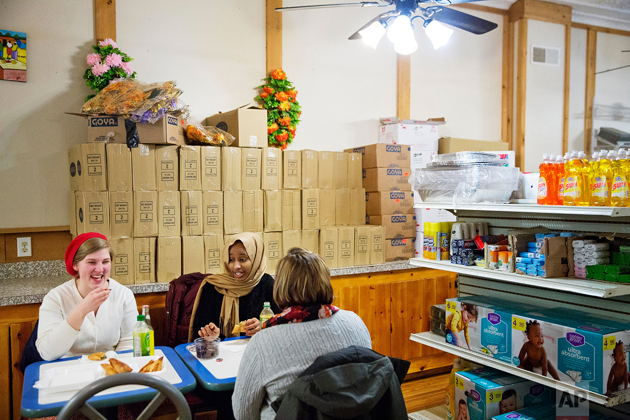 Victoria Schalk, 22, left, and Melinda Blais, 27, right, share a traditional Somali meal with college classmate Nasteho Issa, 21, at restaurant and market opened by one of the first Somali families who settled in 2001 in Lewiston, Maine, Wednesday, March 15, 2017. The population had plummeted in 2001 as the paper mills closed. Downtown storefronts sat boarded up, ringed by sagging apartment buildings no longer needed to house workers since so few remained. The refugees saw possibility in Lewiston's decay. Word spread quickly and friends and families followed, by the hundreds. The town morphed in a matter of months into a laboratory for what happens when demographics and culture suddenly shift. (AP Photo/David Goldman)