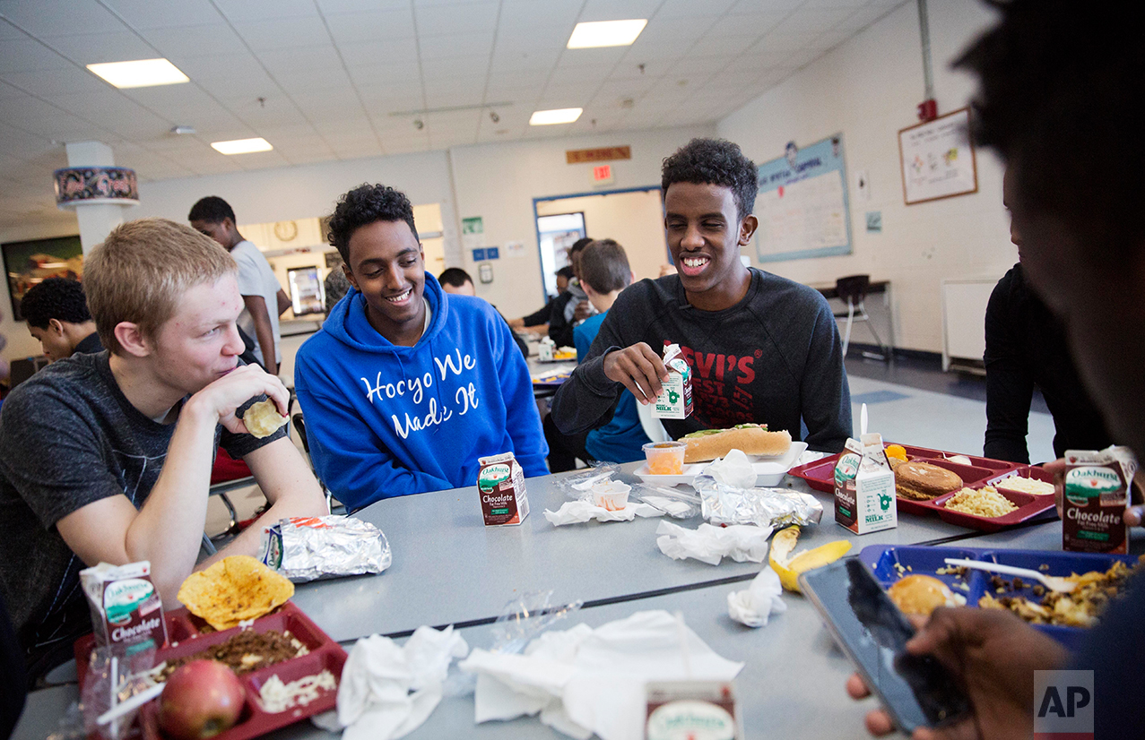 Abdiaziz Shaleh, right, a Lewiston high school senior and co-captain of the soccer team, and Essa Gedi, center, both whose families emigrated from Somalia, sit with classmate Isiah Leach, left, during lunch in the school's cafeteria in Lewiston, Maine, Wednesday, March 15, 2017. Two years ago, immigrant children led the high school soccer team to win the state championship, a moment heralded as a triumph for the city's embrace of its immigrant community. (AP Photo/David Goldman)
