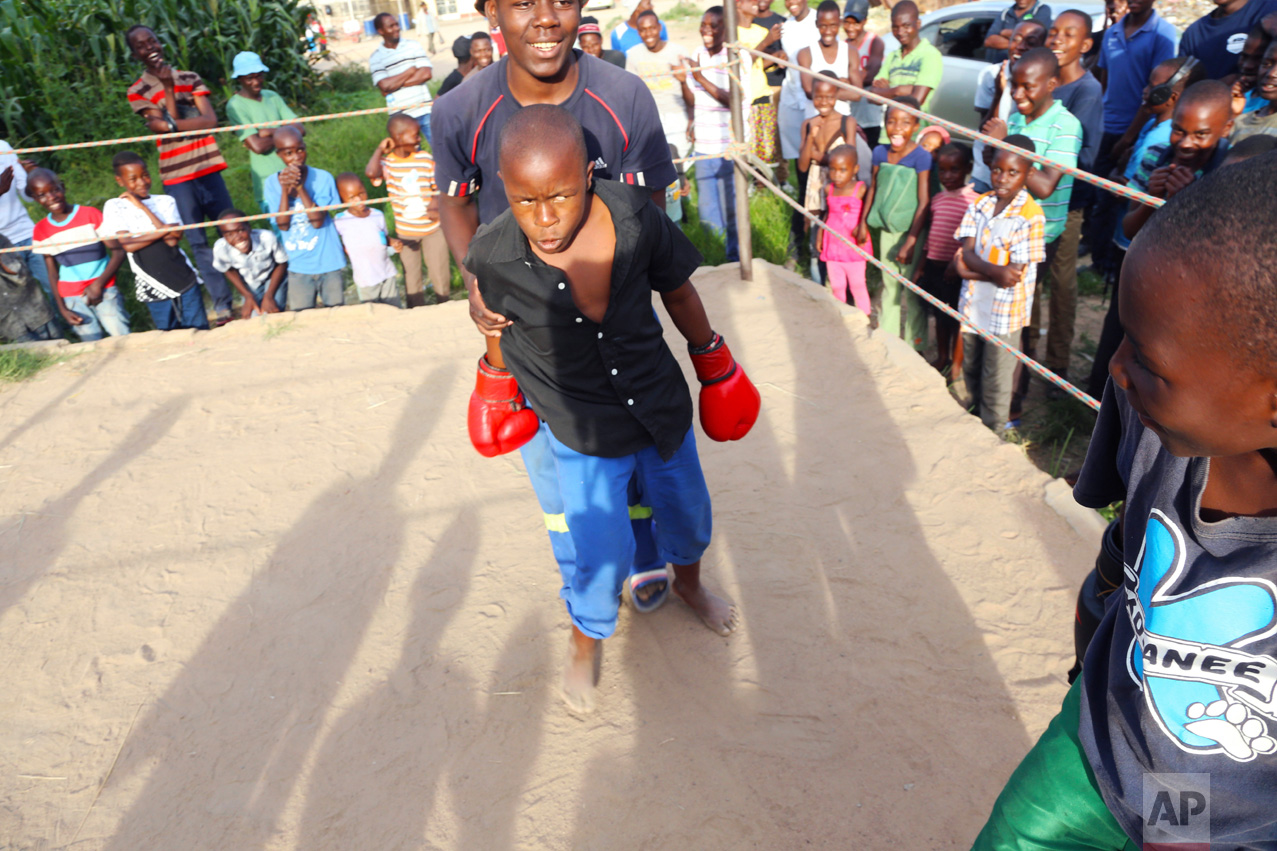 In this Feb. 12, 2017 photo, a young boy is restrained by a referee during a boxing match in Chitungwiza about 30 kilometres south east of Harare. (AP Photo/Tsvangirayi Mukwazhi)
