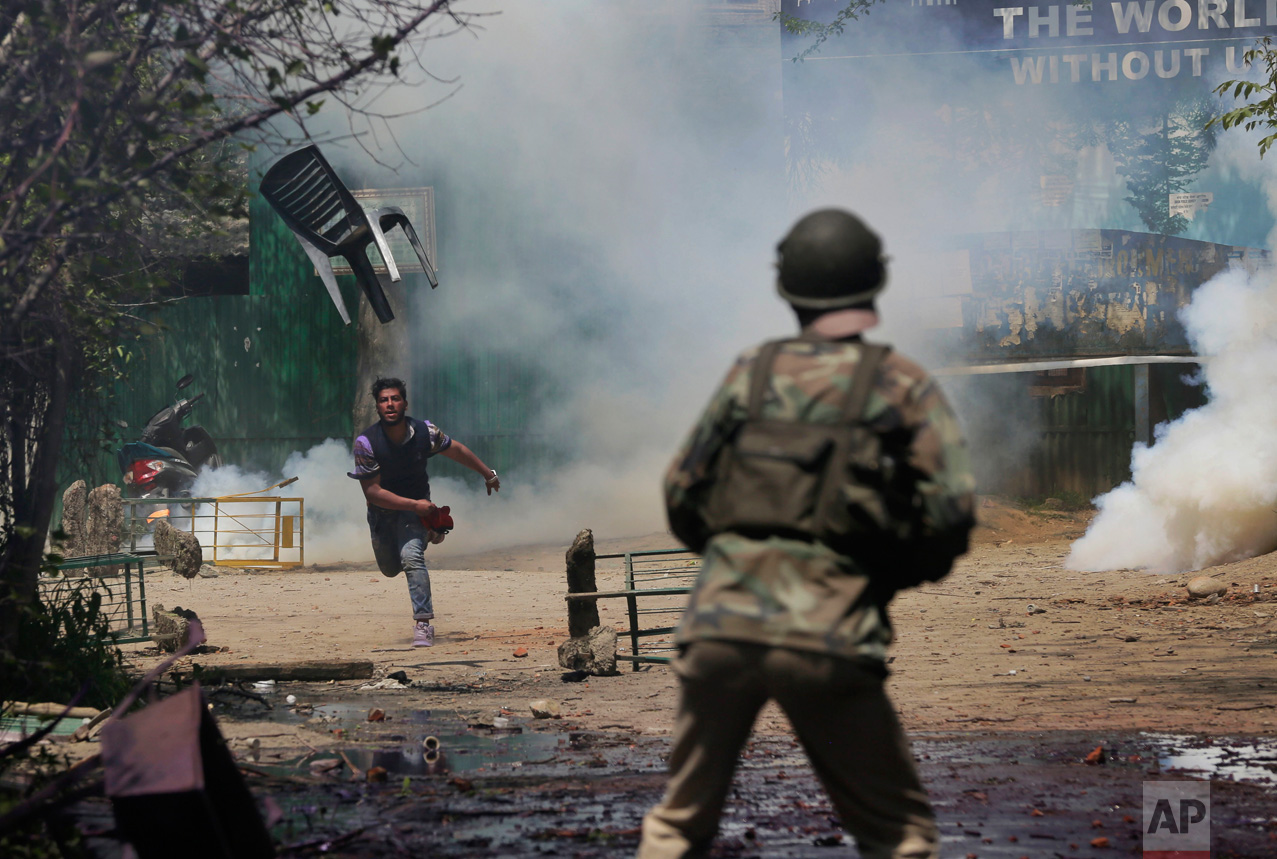 A student throws a chair towards Indian police officers during a clash in Srinagar, Indian controlled Kashmir, on Monday, April 17, 2017. Hundreds of college students took to the streets to protest a police raid in a college in southern Pulwama town over the weekend, in which at least 50 students were injured. (AP Photo/Mukhtar Khan)