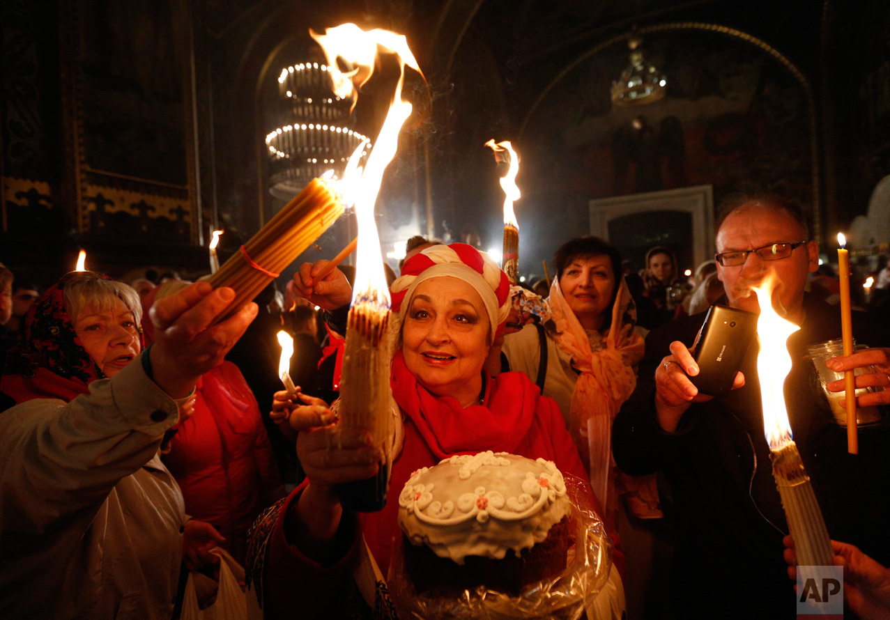 Ukrainian Orthodox worshippers light candles from the Holy Fire brought from Jerusalem in St. Volodymyr Cathedral during the ceremony of the Holy Fire in Kiev, Ukraine, Saturday, April 15, 2017. The ceremony is part of Orthodox Easter rituals and the flame symbolizes the resurrection of Christ in a ceremony dating back to the 12th century. (AP Photo/Sergei Chuzavkov)
