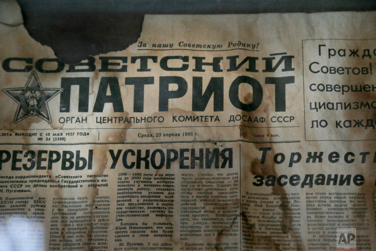 In this photo taken Wednesday, April 5, 2017, an edition of the newspaper Sovetsky Patriot, dated three days before the nuclear explosion, is attached to a bulletin board in a house of culture in the deserted town of Pripyat, some 3 kilometers (1.86 miles) from the Chernobyl nuclear power plant Ukraine. (AP Photo/Efrem Lukatsky)