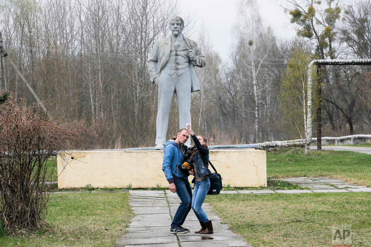 In this photo taken Wednesday, April 5, 2017, journalists take a selfie in front of the monument of Soviet state founder Vladimir Lenin in Chernobyl, Ukraine. (AP Photo/Efrem Lukatsky)