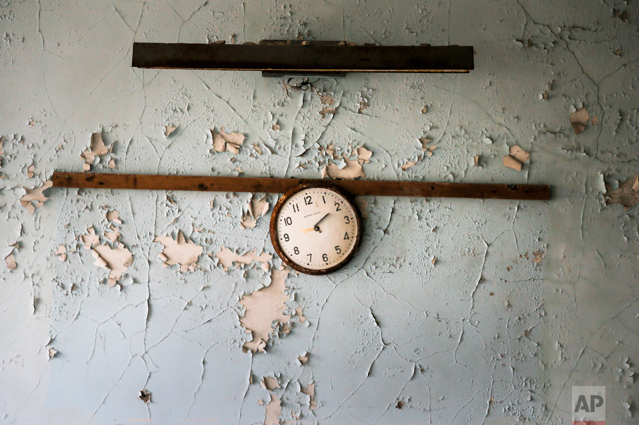 In this photo taken Wednesday, April 5, 2017, a broken clock hangs on a wall in a school in the deserted town of Pripyat, some 3 kilometers (1.86 miles) from the Chernobyl nuclear power plant Ukraine. (AP Photo/Efrem Lukatsky)